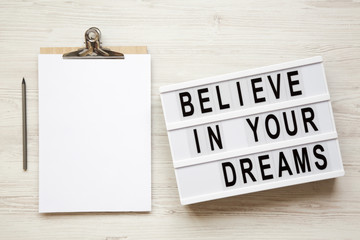 'Believe in your dreams' word on modern board, noticeboard, pencil over white wooden background, overhead. Top view, flat lay, from above.