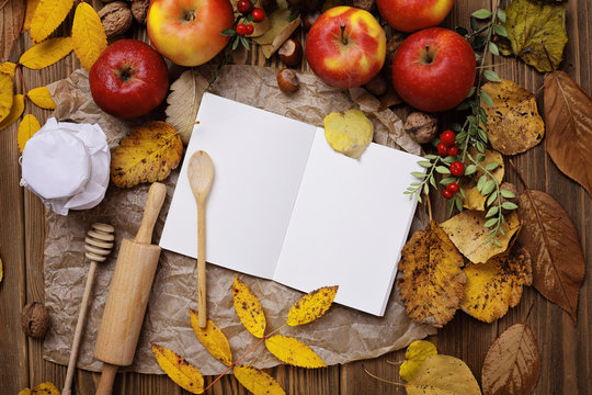 open cookbook and autumn fruits and leaves on wooden background