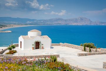 Traditional small whitewash Greek Orthodox Chapel on the edge of Aegean sea.