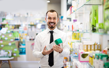 Positive male customer browsing rows of drugs