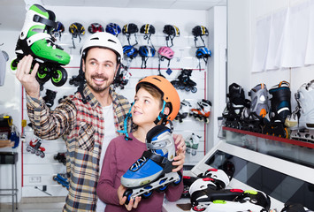 father and son deciding on new roller-skates in sports store