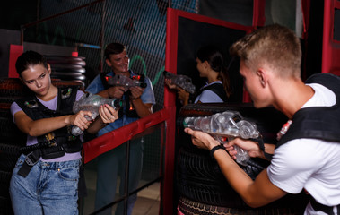 Young friends playing laser tag  game  with  laser guns  together