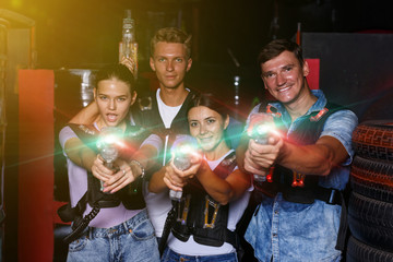 Group of happy young friends with colored laser guns  in dark la