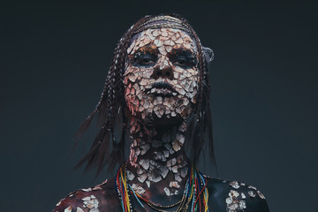 Portrait of a scary African shaman female with a petrified cracked skin and dreadlocks. Make-up concept.