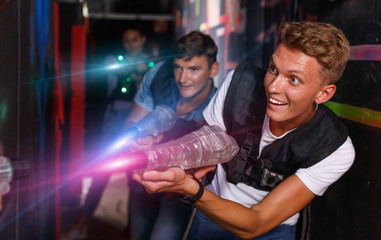 Young guy holding colored laser guns and took aim during laser t