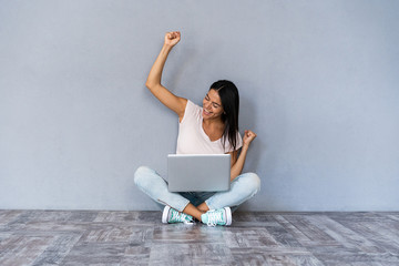Portrait of excited young casual girl celebrating success while sitting with laptop computer isolated over gray background.