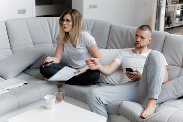 Man watching TV. Woman looking through documents. Lifestyle House Concept
