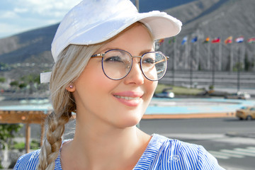 Portrait of a young beautiful woman, blonde in a cap, glasses and with a scythe. On open air.  Close-up.