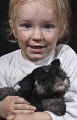 child embracing a puppy
