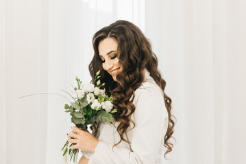 Stylish young pregnant girl in white clothes with curls and flowers.  Photos waiting for baby
