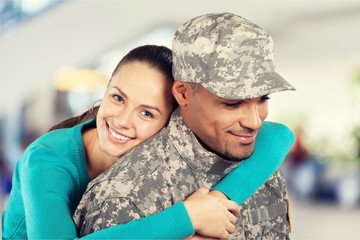 Happy woman hugging military man at home