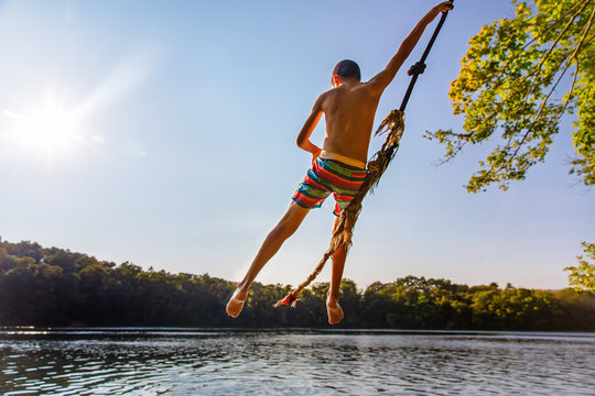 bungee jumping. the boy in free fall over the water. Back view. Copy space for your text