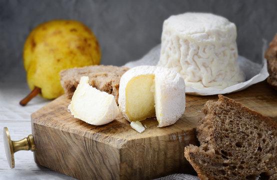 Crottin de Chavignol, French goat cheese on chopping board.