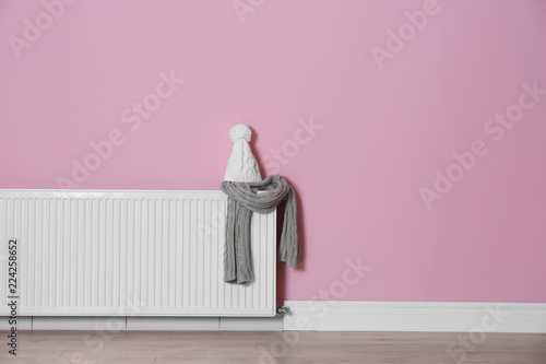 Knitted hat and scarf on modern radiator near color wall with space ...