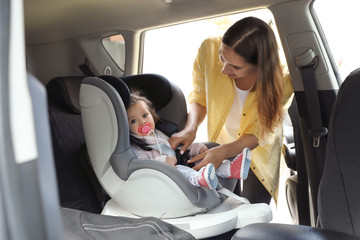 Mother fastening baby to child safety seat inside car