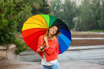 Wall Mural - Happy young woman with bright umbrella under rain outdoors
