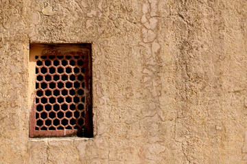 Forts of Rajasthan, ancient sandstone wall textures with a rectangular screened window in Amer, Rajasthan, India.