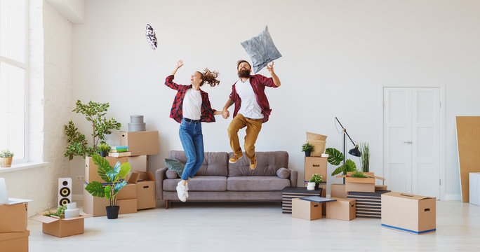 happy young married couple moves to new apartment and laughing,  jump, fight pillows