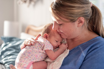 Young mom patting baby girl's back for burp after breastfeeding