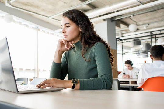 Portrait of pensive young woman using laptop while working in open office, copy space