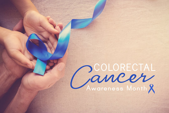 adult and child hands holding Blue ribbon, Colorectal Cancer Awareness month