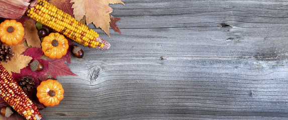 Left corner border of colorful Autumn decorations over a rustic wooden background