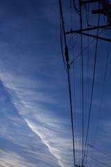 飛行機雲と送電線