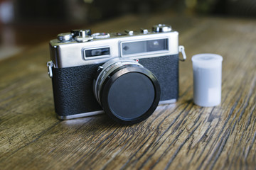 Front view of an old film camera with a lens cap and film canister