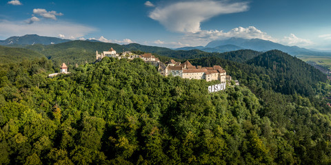 Aerial panorama of Rasnov ruined medieval castle in Transylvania Romania with towers, bastions, walls, barbican and medieval festival
