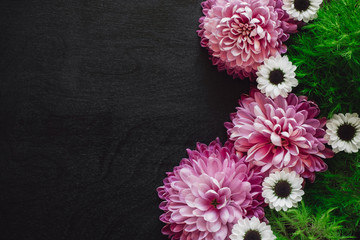 Pink and White Mums with Green Foliage and Space for Copy on Black Table