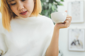 Attractive beautiful asian woman enjoying warm coffee in the kitchen at her home. Asian female wearing comfortable sweater holding a cup of coffee. lifestyle asia woman at home concept.