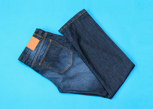 Folded in half men's blue jeans on blue background. The view from the top. Flat lay.