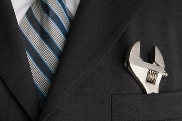 Man wearing a suit with an adjustable wrench in the front pocket