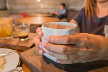 Foto op Plexiglas Bar Female hand holding white cup of coffee ,in coffee shop.