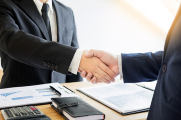 two business men partners shaking hands during a meeting to deal complete to sign agreement contract and become success in the office.