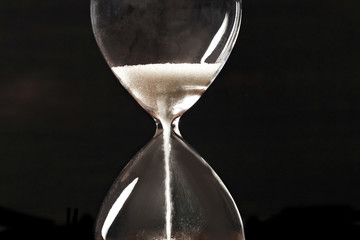 A closeup of an hourglass with falling sand, on a dark background with copy space Wall mural