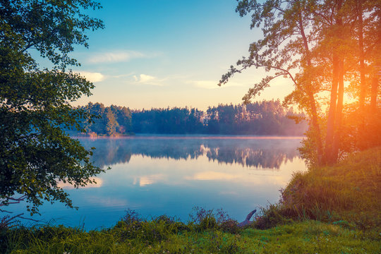 Early morning, sunrise over the lake. Rural landscape, wilderness. Beautiful nature of Finland, Europe