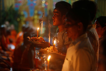 People hold offerings while praying for loved ones who have passed away during the first day of Pchum Ben festival, or the festival of the dead in Phnom Penh