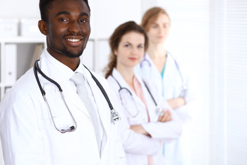 Happy african american male doctor  with medical staff at the hospital. Medicine concept