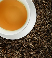 Cup of White Tea on the Dried White Tea Leaves - Top View