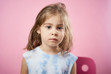 isolated cute little girl in a dress posing on a pink background