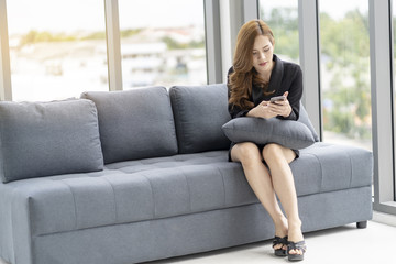 Businesswoman sat at the sofa, checking the information on the mobile phone.