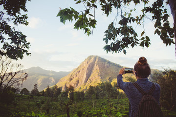 Girl tourist photographing mountains in Sri Lanka