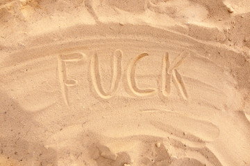 """Expression of discontent. """"FUCK"""" on the sand."""
