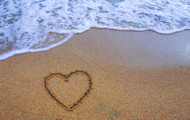Heart on sand beach with white wave,symbol of love,beautiful sea background,handwritten,valentine