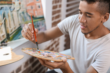 Young African-American artist painting picture in workshop