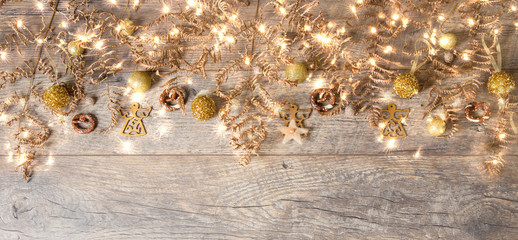 Golden Christmas decorations on shiny background with copy space for text. Christmas background or greeting card. Selective focus. Golden banner