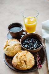 Simple breakfast: coffee americano, fresh buns with jam and juice.
