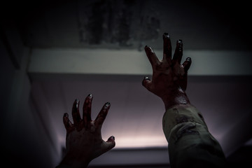 .Zombie stretching bloody hands in dark room