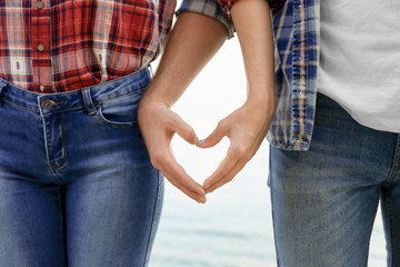 Cute young couple making heart with their hands on sea shore, closeup